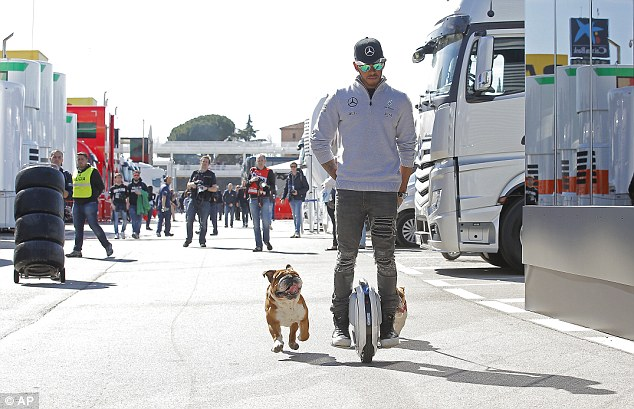 Lewis Hamilton sports ripped jeans and branded fleece as he rides unicycle around Barcelona with pet dogs